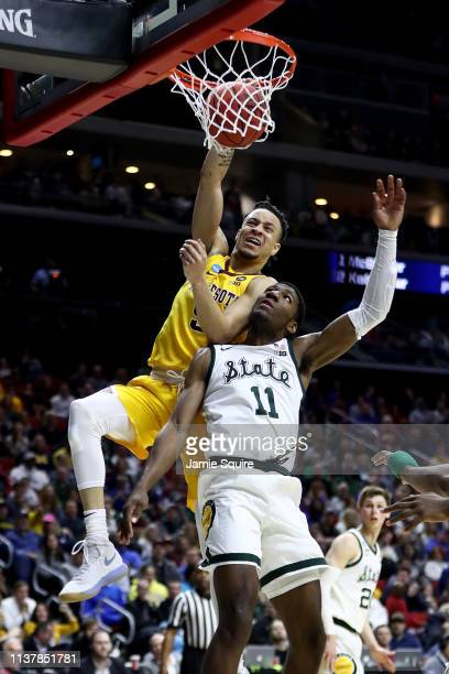 Amir Coffey of the Minnesota Golden Gophers dunks the ball against Aaron Henry of the Michigan State Spartans during the first half in the second...