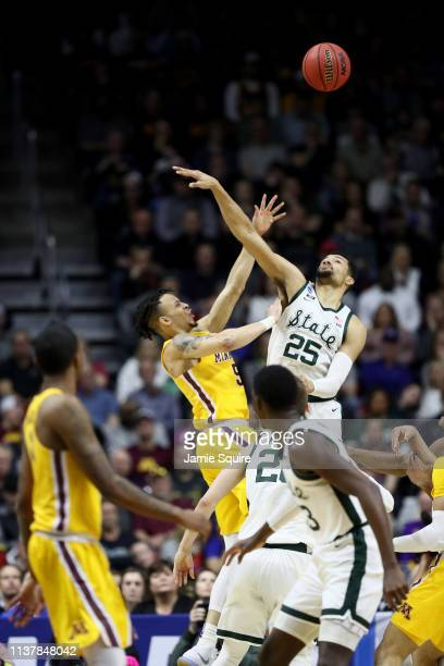 Amir Coffey of the Minnesota Golden Gophers shoots the ball against Kenny Goins of the Michigan State Spartans during the first half in the second...