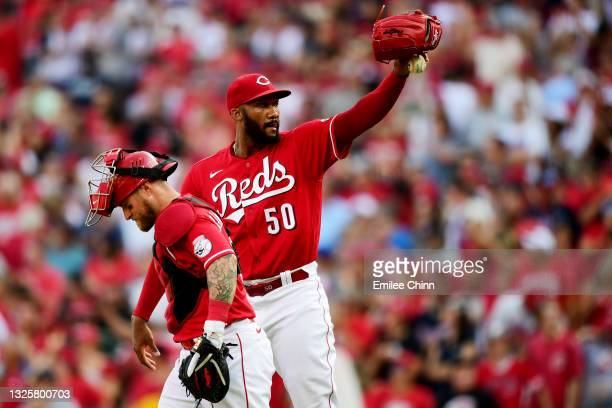 Amir Garrett and Tucker Barnhart of the Cincinnati Reds react to their 4-1 win over the Atlanta Braves at Great American Ball Park on June 26, 2021...