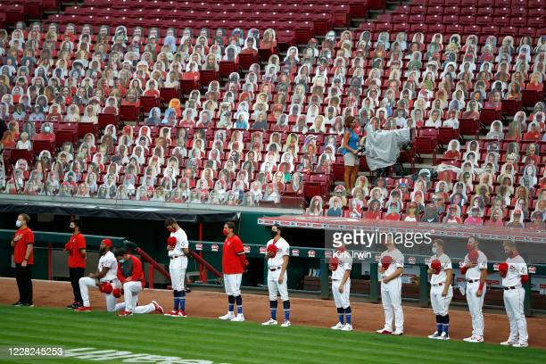 Amir Garrett of the Cincinnati Reds and Jesse Biddle kneel during the playing of the national anthem prior to the start of the game against the...