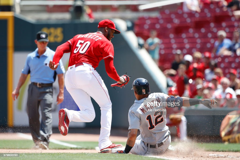 Amir Garrett #50 of the Cincinnati Reds steps on first base ahead of the slide by Leonys Martin #12 of the Detroit Tigers in the seventh inning at Great American Ball Park on June 20, 2018 in Cincinnati, Ohio. The Reds won 5-3.