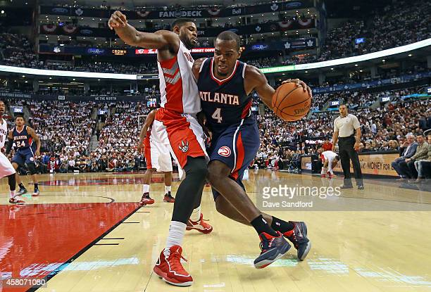 Amir Johnson of the Toronto Raptors defends against Paul Millsap of the Atlanta Hawks drives to the basket during their NBA game at the Air Canada...