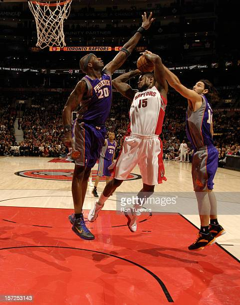 Amir Johnson of the Toronto Raptors looks to pass the ball against Jermaine O'Neal and Luis Scola of the Phoenix Suns on November 30 2012 at the Air...