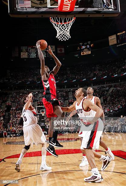 Amir Johnson of the Toronto Raptors shoots a layup against Juwan Howard Rudy Fernandez and Marcus Camby of the Portland Trail Blazers during the game...