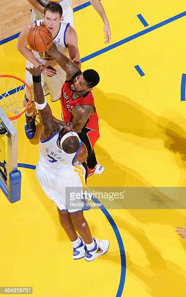 Amir Johnson of the Toronto Raptors shoots against Jermaine O'Neal of the Golden State Warriors on December 3 2013 at Oracle Arena in Oakland...
