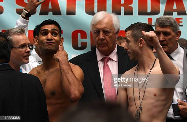 Amir Khan makes a gesture as Paul McCloskey looks on during the official weigh in ahead of their WBA lightwelterweight fight at the Triangle Shopping...