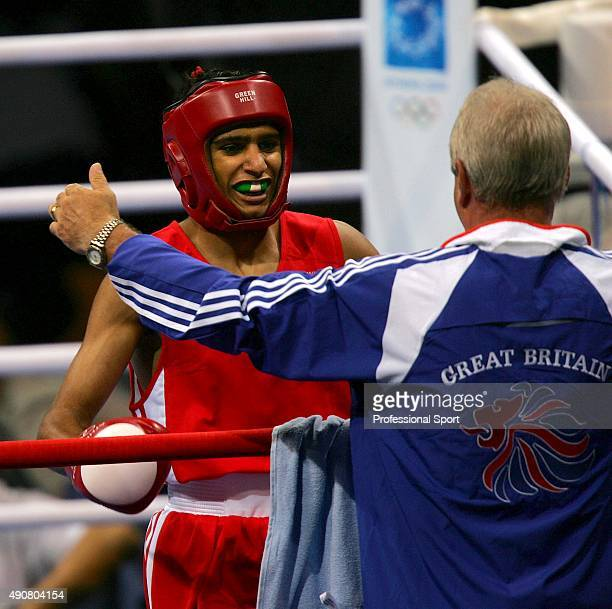 Amir Khan of Great Britain hugs his coach Terry Edwards after defeating Jong Sub Baik of Korea during the men's boxing 60 kg quarterfinal bout on...
