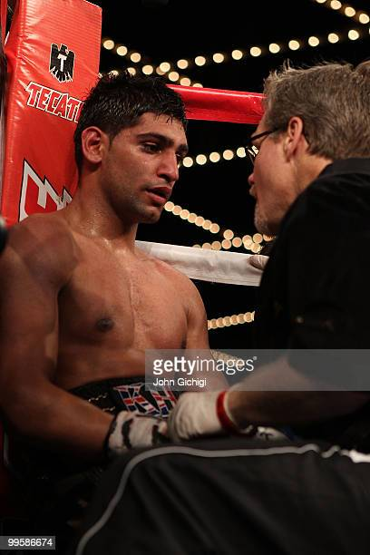 Amir Khan of Great Britain talks with his trainer Freddie Roach in his corner during the WBA light welterweight title fight against Paulie Malignaggi...