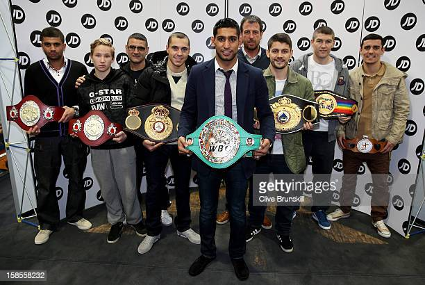 Amir Khan poses with his WBC Silver superlightweight belt and all of the professional and amateur belt winners from his Gloves gym during a media day...