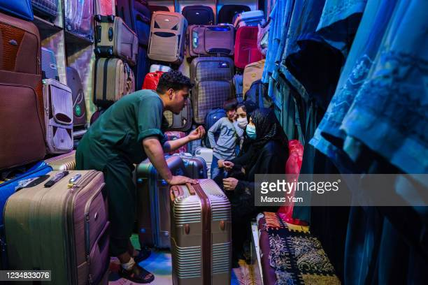 Amir Saib Zada negotiates with customers at their store that sells luggages and burkas, in the Lycee Maryam Bazaar in the Khair Khana neighborhood,...