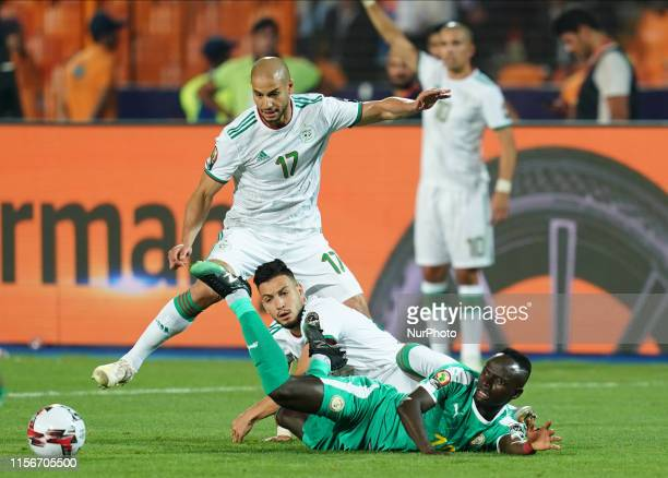 Amir Selmane Rami Bensebaini of Algeria fouling Sadio Mane of Senegal during the Final of 2019 African Cup of Nations match between Algeria and...