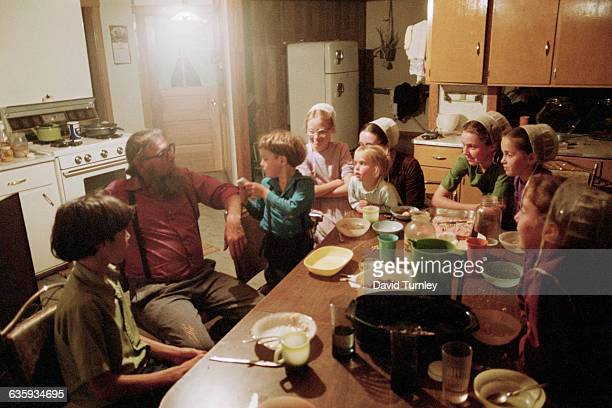 Amish children crowd around their father after a meal in the kitchen | Location Near Shipshewana Indiana USA
