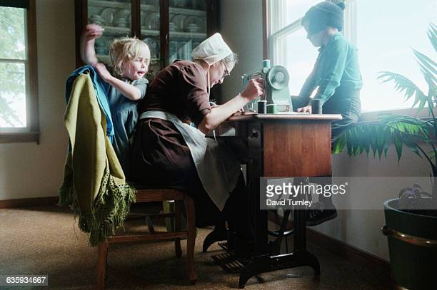 Amish children not yet school age watch their mother as she sews with her treadle sewing machine The Amish in the Shipshewana area of Indiana do not...