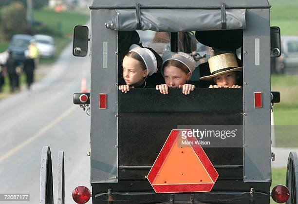 Amish children ride in the back of a buggy as they travel to a wake at the home of two of the Amish school shooting victims October 3 2006 in Nickel...