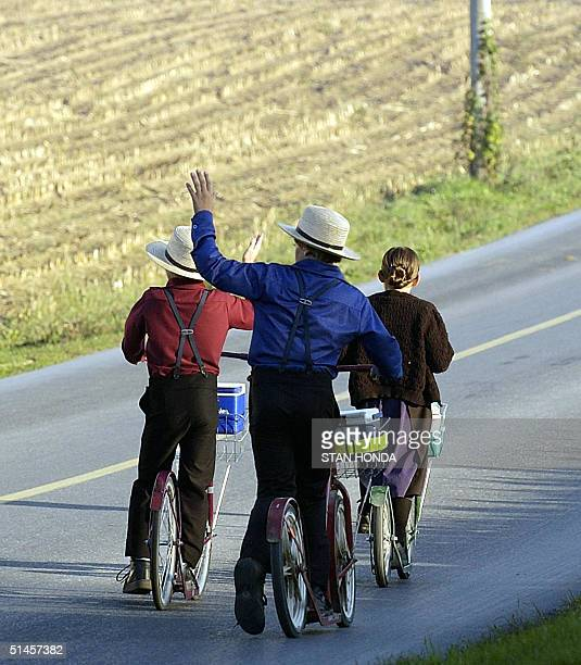 Amish children wave to a neighbor as they push their scooters on the way to school 08 October near BirdinHand Pennsylvania Amish are descendants of...