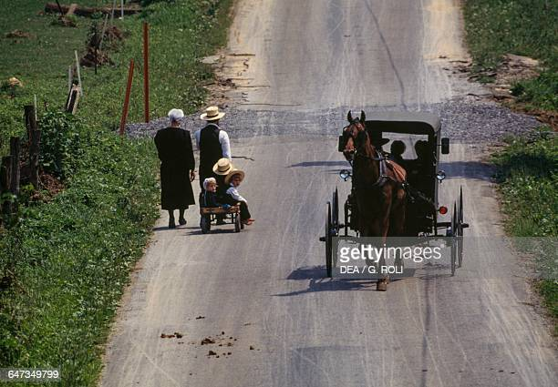 Amish families passing on the road one on foot and the other on horsedrawn carriage Lancaster Pennsylvania United States of America