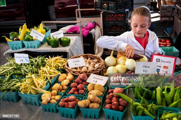 Amish girl selling produce in market