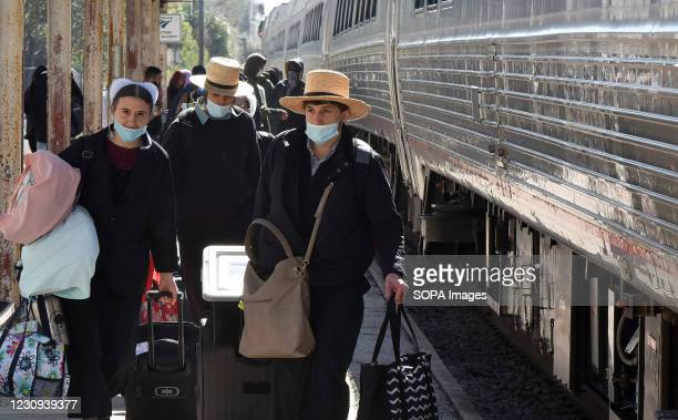 Amish rail passengers wearing face masks walk on the platform after exiting a train at the Orlando Amtrak station on the first day that the...