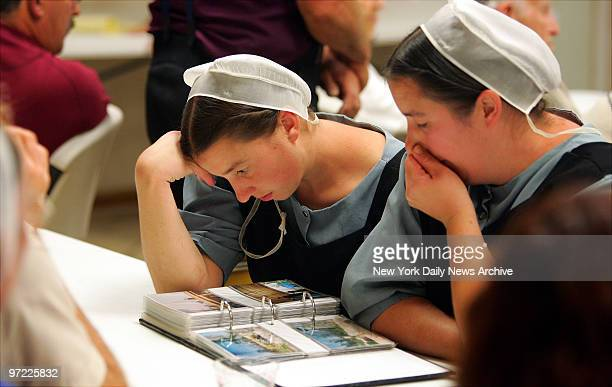 Amish women react with emotion as they look over photographs of Waveland Miss as it was before Hurricane Katrina hit during a sharing night for the...