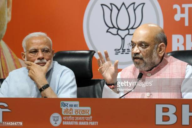 Amit Shah president of Bharatiya Janata Party right speaks as Narendra Modi India's prime minister looks on during a news conference at the BJP...