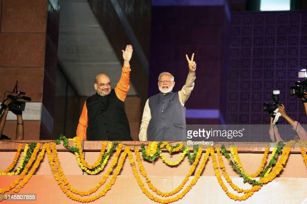 Amit Shah president of the Bhartiya Janata Party left and Narendra Modi India's prime minister gesture to the crowd during an event at the party's...