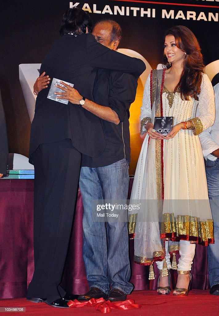 Amitabh Bachchan hugs actor Rajinikanth and Aishwarya Rai looks on during the music launch of the film `Robot` in Mumbai on August 14 2010