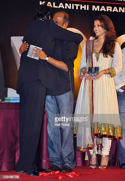 Amitabh Bachchan hugs actor Rajinikanth and Aishwarya Rai looks on during the music launch of the film 'Robot' in Mumbai on August 14 2010