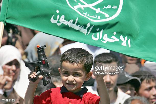 Jordanian child holds a toy gun under a flag of Jordan's Muslim Brotherhood during a demonstration after Friday prayers to condemn the massive...