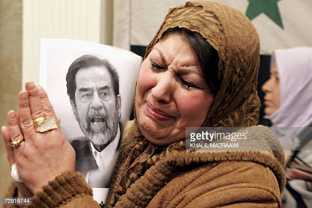 A Jordanian woman cries as she holds a portrait of executed former Iraqi leader Saddam Hussein during a rally at the Professional Unions' Association...