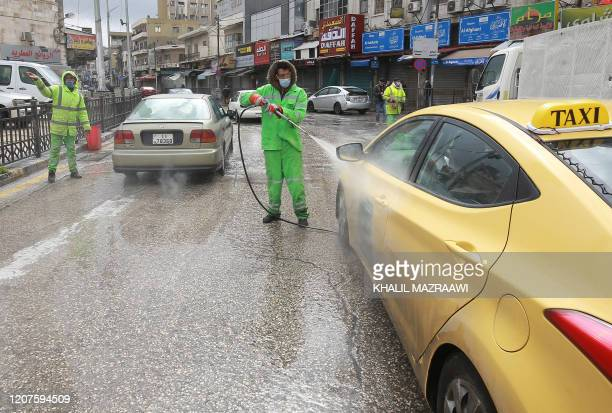 Amman municipality workers spray cars with sanitisers in the Jordanian capital on March 18 2020 amidst measures to fight the spread of the...