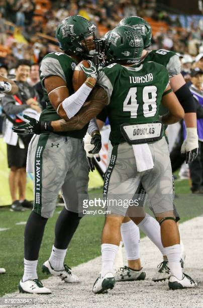 Ammon Barker of the Hawaii Rainbow Warriors celebrates with teammates Ryan Tuiasoa and Chris Posa after scoring a touchdown during the second half of...