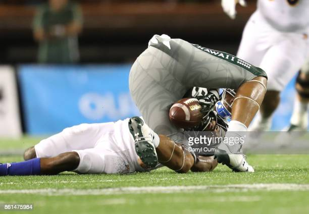 Ammon Barker of the Hawaii Rainbow Warriors rolls over as he tries to hold on to the ball during the second quarter of the game against the San Jose...