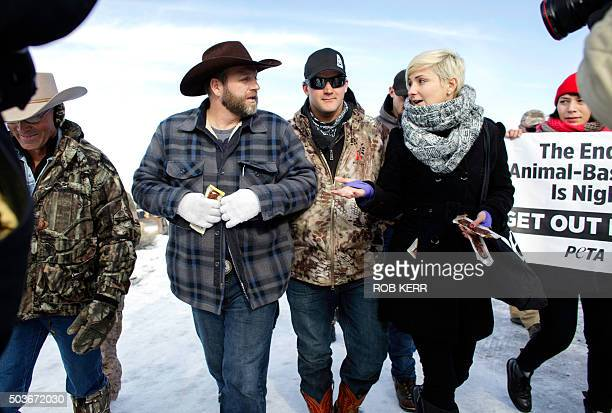 Ammon Bundy is presented with a meatless jerky snack by PETA representative Lindsay Rajt as he makes his way from the entrance of the Malheur...