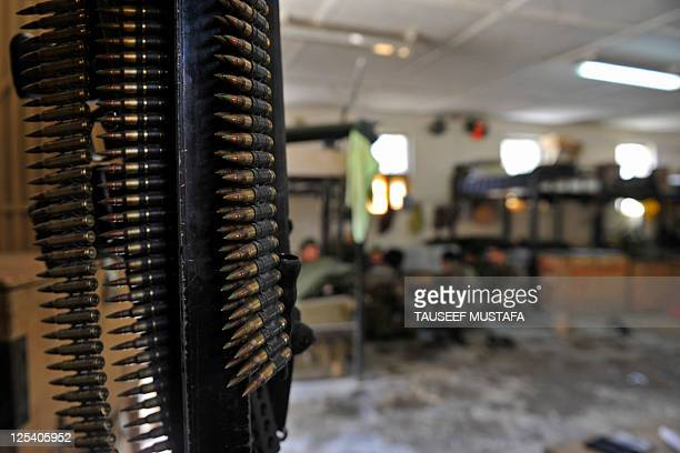 Ammunition belts are seen hanging from a bunk bed as Afghan National Army soldiers eat in their quarters at Combat Outpost Monti in Kunar province on...