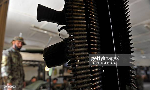 Ammunition belts are seen hanging from a bunk bed as an Afghan National Army soldier looks on at Combat Outpost Monti in Kunar province on September...
