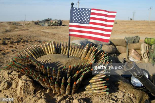 Ammunition for a SAW machine gun surrounds a US flag at the defensive position of Task Force Tarawa April 2 2003 in the southern Iraqi city of...