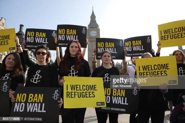 Amnesty International activists hold placards as they protest against US President Donald Trump's Travel ban in Parliament Square on March 16 2017 in...