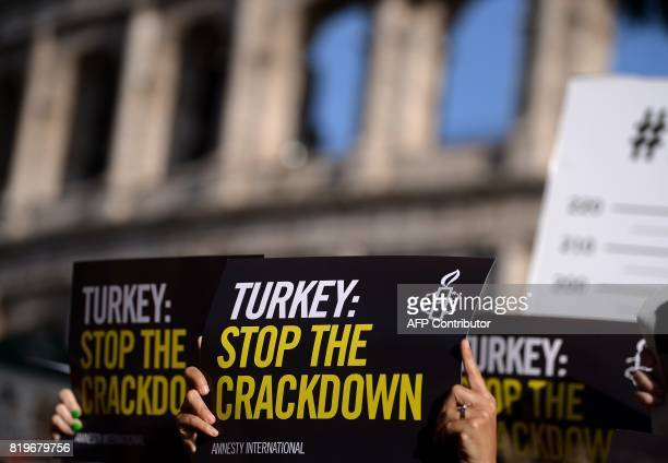 Amnesty International activists hold placards as they protest against the arrest of rights activists in Turkey including Amnesty International's...