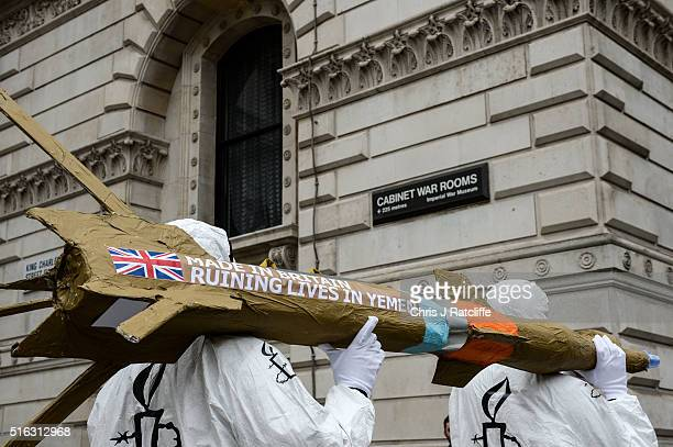 Amnesty International activists march with homemade replica missiles bearing the message 'Made in Britain destroying lives in Yemen' past the cabinet...