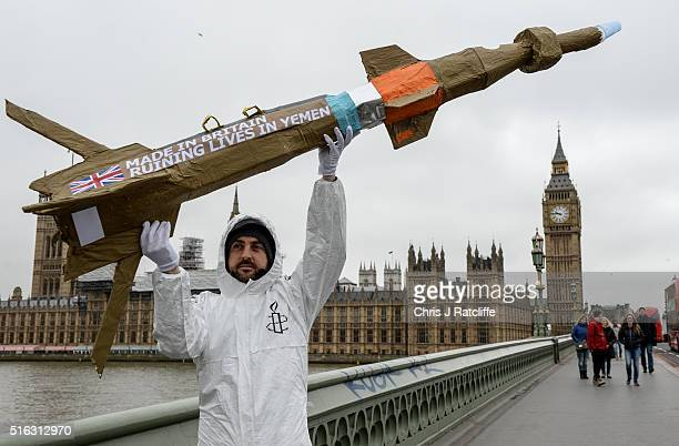 Amnesty International activists march with homemade replica missiles bearing the message 'Made in Britain destroying lives in Yemen' across...