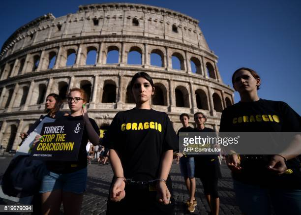 Amnesty International activists wear handcuffs as they protest against the arrest of rights activists in Turkey including Amnesty International's...