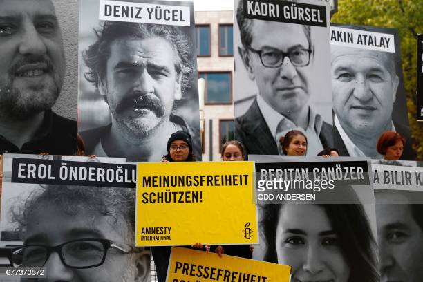 Amnesty International and 'Reporters without Borders' activists pose with portraits of Turkish journalists detained in Turkey and banners in front of...