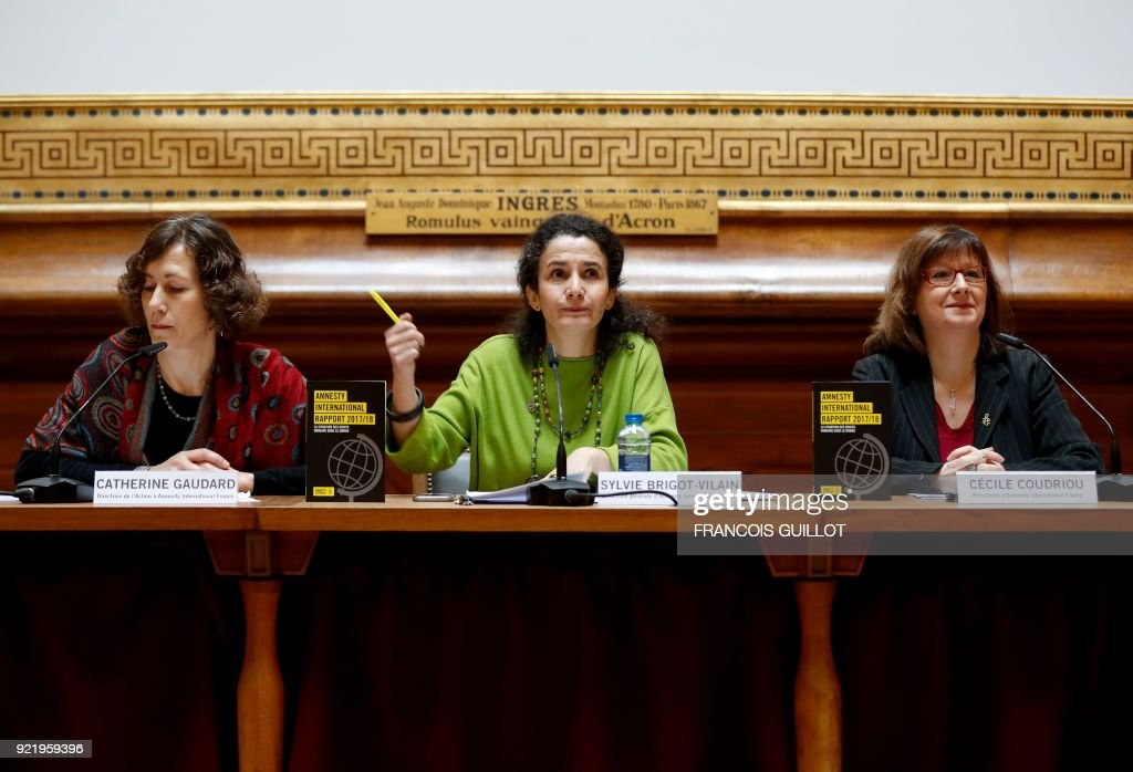 Amnesty International France's director Sylvie Brigot-Vilain (C), Amnesty International France's President Cecile Coudriou (R) and Amnesty International France's Head of Campaigns Catherine Gaudart (L) give a press conference for the release of the INGO annual report in Paris on February 21, 2018. /