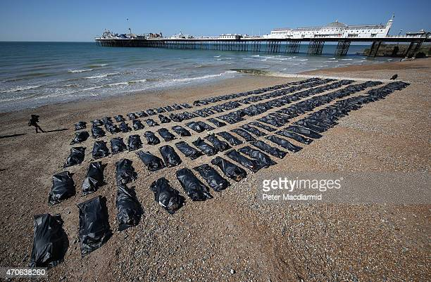 Amnesty International volunteers lie in a body bags on the beach on April 22 2015 in Brighton England The charity placed two hundred body bags next...