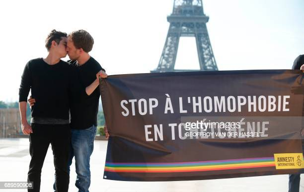 Amnesty militants kiss each others as they hold a banner reading 'Stop homophobia in Chechnya' to denounce persecution against LGBT community in...