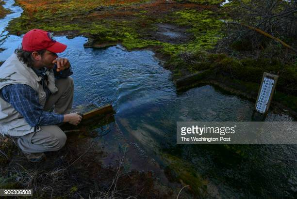 Amo Oliverio checks a flowrate table as he walks through the wetlands contaminated with acid mine drainage at the Kempton abandoned mine complex on...