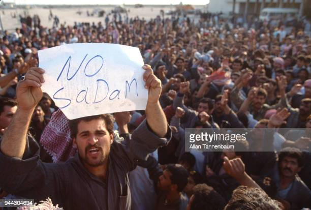 Among a large group a man holds up a handwritten sign that reads 'No Sadam' during a Gulf War demonstration Iraq 1991