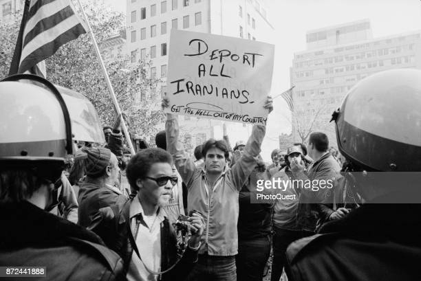 Among a larger group a protestor holds a sign that reads 'Deport All Iranians Get Out of My Country' during a demonstration about the Iran Hostage...