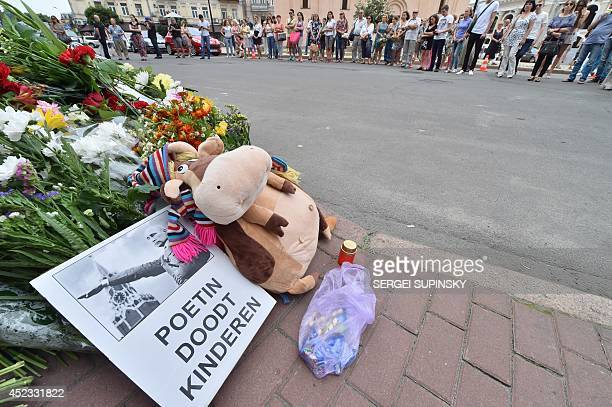 Among flowers and candles a banner reading in Dutch 'Putin kill children' as been displayed in front of the Netherlands Embassy in Kiev on July 18...