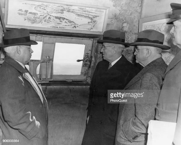 Among others American politician US President Harry S Truman and Secretary of the Interior Harold L Ickes look out of an observation window atop the...